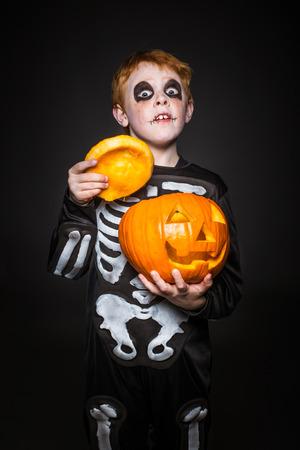 Surprised red haired child in skeleton costume holding a orange pumpkin. Halloween. Studio portrait over black background 스톡 콘텐츠