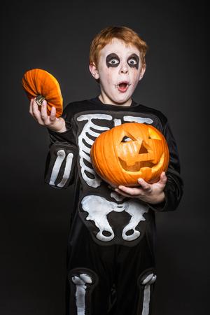 Verrast rood haar kind in Halloween kostuum met een oranje pompoen. Skelet. Studio portret op zwarte achtergrond Stockfoto