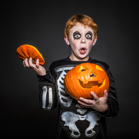 Surprised red hair boy in Halloween costume holding a orange pumpkin. Skeleton. Studio portrait over black background