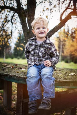 Beautiful blond kid sitting outdoor on table. Autumn. Outdoor portrait