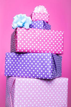 Kleurrijke geschenkdozen met lint over roze achtergrond. Roze, paars, pastel, helder. Studio-opname Stockfoto