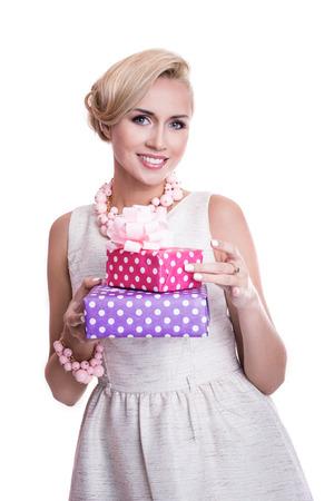 Mooie blonde vrouw met mooie make-up met paarse en roze geschenkdozen. Studio portret geïsoleerd op witte achtergrond