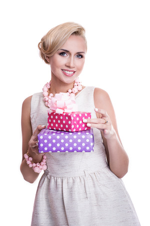 Nice blonde woman with beautiful makeup holding purple and pink gift boxes. Studio portrait isolated over white background