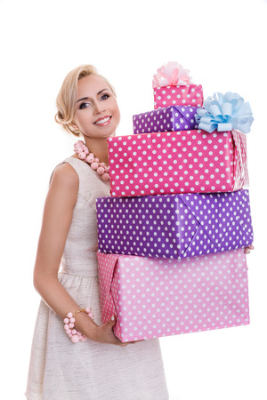 Beautiful blonde woman with a colorful gift boxes. Studio portrait isolated over white background