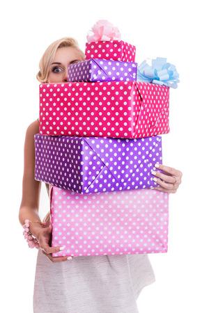 Mooie blondevrouw die door kleurrijke giftdozen kijken. Studio portret geïsoleerd op witte achtergrond