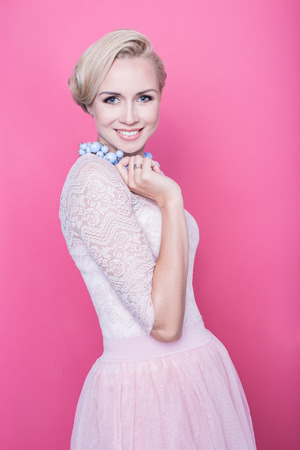 Fashion shot of young beautiful woman with gorgeous cream colored dress. Studio portrait over pink background