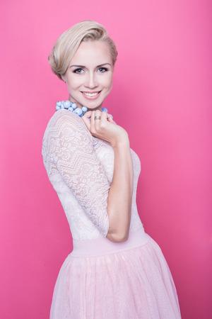 Fashion shot van jonge mooie vrouw met prachtige crèmekleurige jurk. Studio portret over roze achtergrond