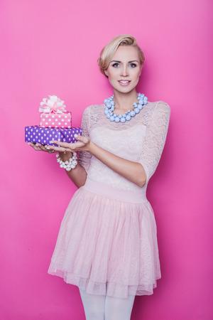 Hermosa mujer rubia con vestido de color crema celebración rosa y cajas de regalo de color púrpura. Retrato de estudio sobre fondo de color rosa brillante Foto de archivo - 33637623
