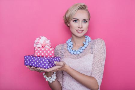 Fashion shot van jonge mooie vrouw met roze en paarse geschenkdozen. Studio portret over heldere roze achtergrond