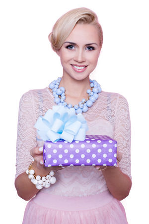 Blonde woman with beautiful smile giving colorful gift box. Christmas. Holiday. Studio portrait isolated over white background 스톡 콘텐츠