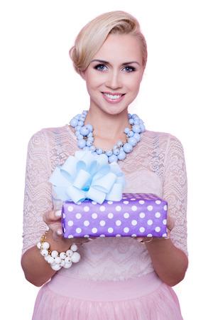 Blonde vrouw met een mooie glimlach geven kleurrijke geschenkdoos. Kerstmis. Vakantie. Studio portret geïsoleerd op witte achtergrond