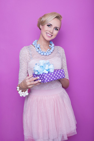 Woman with big beautiful smile holding purple present. Christmas. Holiday. Gift. Studio portrait over purple background 스톡 콘텐츠