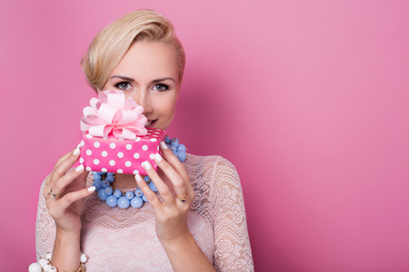 gifts: Happy birthday. Sweet blonde woman holding small gift box with ribbon. Soft colors. Studio portrait over pink background