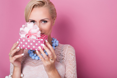 Merry christmas. Beautiful blonde woman holding small gift box with ribbon. Soft colors. Studio portrait over pink background