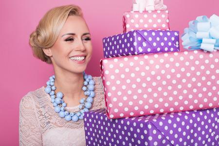 Vrouw met grote mooie glimlach bedrijf kleurrijke geschenkdozen. Zachte kleuren. Kerstmis, verjaardag, Valentijn, presenteert. Studio portret over roze achtergrond Stockfoto