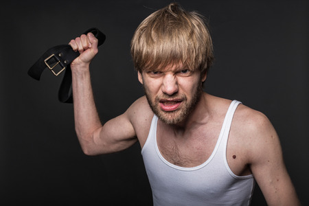 wife beater: Concept: violence in the family. Studio portrait over black background
