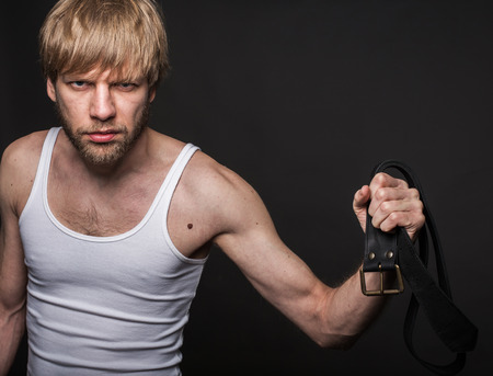 wife beater: Angry man threatens with belt. Concept: Violence in the family. Studio portrait over black background Stock Photo