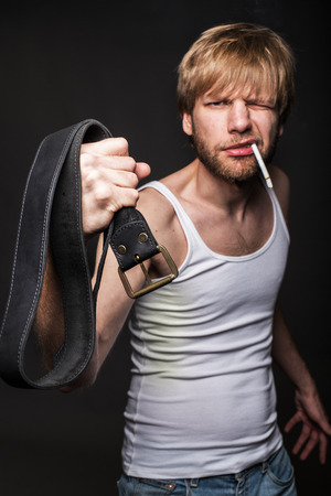 wife beater: Angry man threatens with belt. Concept: Violence against women. Studio portrait over black background