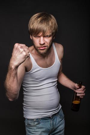 threaten: Drunk man threaten with fist. Studio portrait over black background Stock Photo