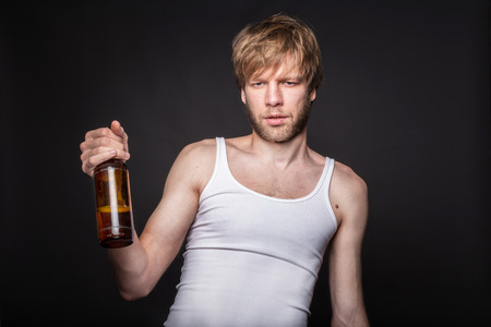 Concept: alcohol addiction. Hangover. After party. Studio portrait over black background