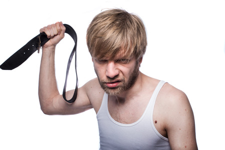 wife beater: Angry man threatens with belt. Concept: Violence in the family. Abuse. Studio portrait isolated over white background