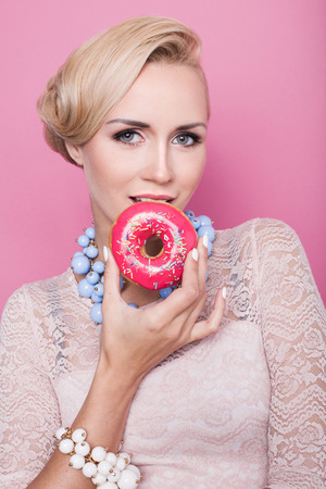 white sugar: Beautiful middle aged women tasting colorful donut. Soft colors. Studio portrait over pink background