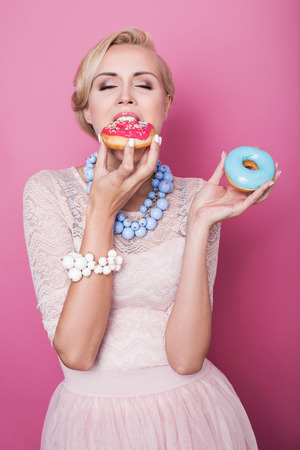 over eating: Beautiful blonde women eating colorful dessert. Fashion shot. Soft colors. Studio portrait over pink background