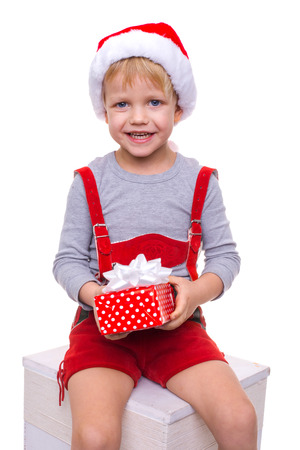 dwarf costume: Little blond kid in red costume of dwarf holding gift box with ribbon. Christmas. Studio portrait isolated over white background Stock Photo