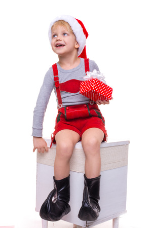 dwarf christmas: Little child in red costume of dwarf holding gift box with ribbon and looking up. Christmas. Studio portrait isolated over white background Stock Photo