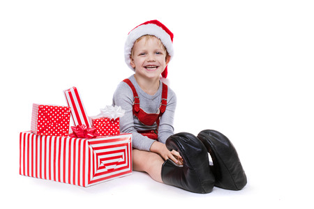 dwarf christmas: Concept: Christmas in childhood. Kid in red costume of dwarf with gifts. Studio portrait isolated over white background