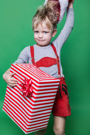 dwarf christmas: Kid in red costume of dwarf holding Christmas gift and throws Santa Claus cap. Naughty child. Studio portrait over green background Stock Photo