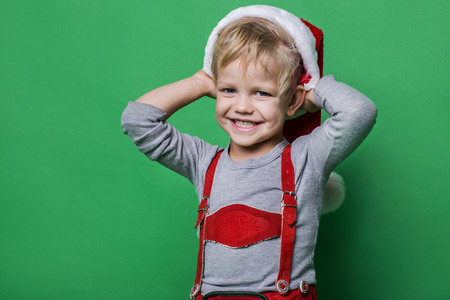 Beautiful little boy dressed like Santa Claus helper smiling. Christmas concept. Studio portrait over green background photo
