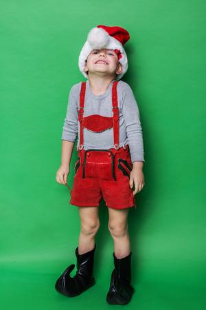 dwarf costume: Little child with Christmas dwarf costume. Studio portrait over green background