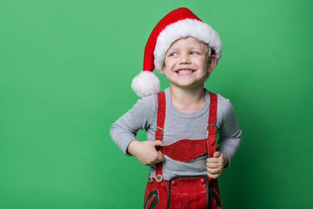 elf: Beautiful little boy dressed like Christmas elf with big smile. Christmas concept. Studio portrait over green background