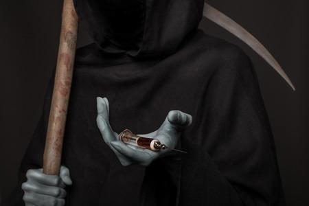 概念: 薬を殺します。死の天使のヘロインを注射器を保持しています。黒の背景にわたって撮影スタジオ
