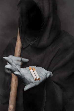 The concept: smoking kills. Angel of death holding cigarette photo