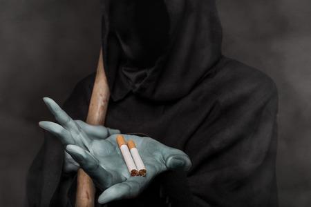 The concept: smoking kills. Grim reaper holding cigarette photo