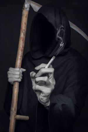 The concept: smoking kills. Grim reaper holding cigarette. Studio shot over black background photo