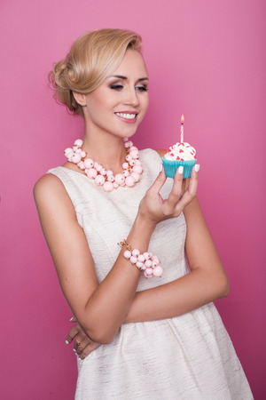 party food: Nice blonde woman holding cake with candle. Birthday, holiday. Studio portrait over pink background Stock Photo