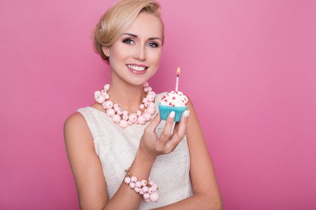 Beautiful young women holding small cake with colorful candle. Birthday, holiday. Studio portrait over pink background 스톡 콘텐츠