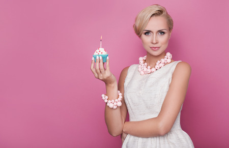 woman blowing: Happy Birthday. Beautiful young women holding small cake with colorful candle. Studio portrait over pink background