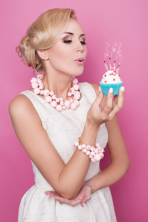 Elegant woman blowing out candles on birthday cake. Studio portrait over pink background