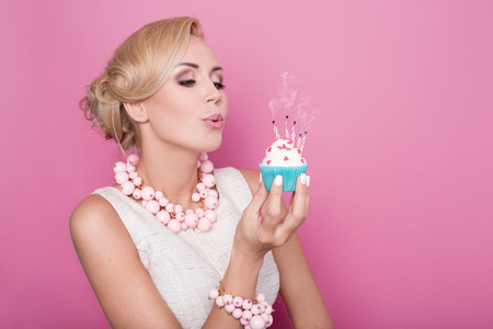 girl blowing: Beautiful women with cream dress holding small cake with colorful candle. Birthday, holiday. Studio portrait over pink background