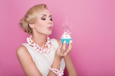 urodziny: Piękne kobiety z kremowa sukienka gospodarstwa małe ciasto z kolorowych świec. Urodziny, wakacje. Portret studio na różowym tle Zdjęcie Seryjne