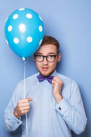 Attractive young man with a blue balloon in his hand. Party, birthday, Valentine. Studio portrait over blue background