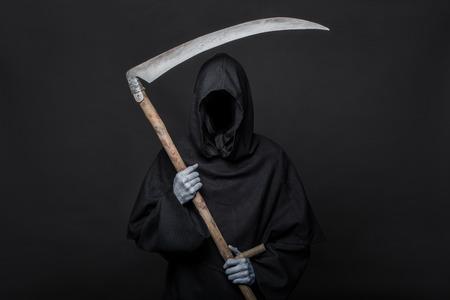 Dood reaper over zwarte achtergrond. Halloween. Studio portret op zwarte achtergrond Stockfoto