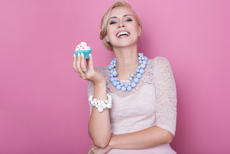 Laughing beautiful women hold little colorful cake. Soft colors. Studio portrait over pink background