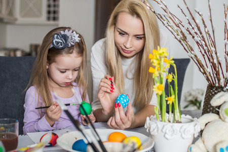 Girl with her mother learning to paint Easter eggs. Cozy home atmosphere. Easter photo