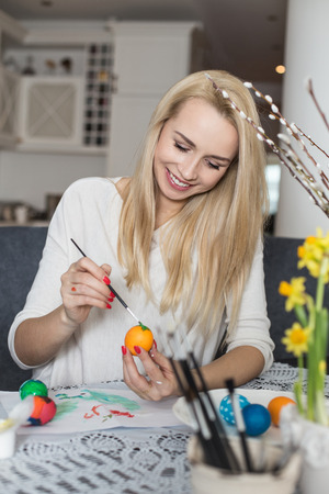 Beautiful young woman painting easter eggs. Cozy home atmosphere. Easter