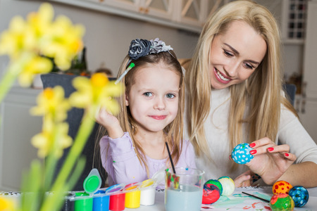 Young mother and her beautiful daughter painting Easter eggs. Easter, family, holiday and child concept photo